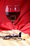Corchos, sacacorchos y vidrio del vino con las uvas de vino rojo en la tabla de madera Imagenes de archivo