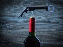 Corckscrew sur la bouteille de vin rouge photographie stock libre de droits