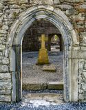 Old stone portal with cross in the background, Corcomroe Abbey, County Clare, Ireland. Corcomroe Abbey is an early 13th-century Cistercian monastery located in Royalty Free Stock Photography