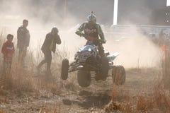 Corcunda excedente transportada por via aérea da bicicleta do quadrilátero na fuga da poeira no duri da trilha da areia Foto de Stock