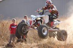 Corcunda excedente transportada por via aérea da bicicleta do quadrilátero na fuga da poeira no duri da trilha da areia Imagens de Stock