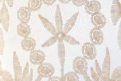 Cordón beige apacible del primer con adornos florales en el backgroun blanco Fotos de archivo libres de regalías