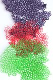 Cordón coralino del crespón púrpura, rojo y verde en el fondo blanco imagenes de archivo