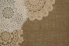 Cordón del tapetito del ganchillo en el fondo de lino Imagen de archivo