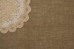 Cordón del tapetito del ganchillo en el fondo de lino Fotografía de archivo libre de regalías