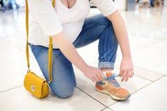 Cordón joven de la mujer embarazada encima de las zapatillas de deporte en el pasillo del centro comercial Los problemas de mujer imagenes de archivo