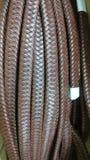 Cordón plano del cuero de Brown en el fondo blanco Foto de archivo
