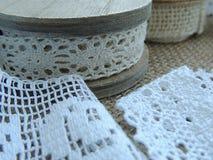 Cordón poner crema en la bobina de madera, cordón blanco del vintage en fondo de la arpillera Fotografía de archivo