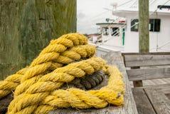 Corda amarela envolvida em torno do cargo no cais Imagens de Stock Royalty Free