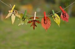Corda com folhas e soletração das letras: OUTONO Foto de Stock