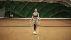 Corda de salto atrativa do atleta fêmea em um campo de tênis interno handicap Front View Movimento lento video estoque