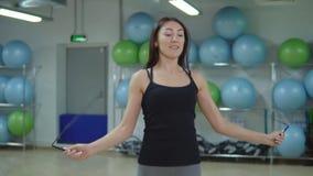 Corda de salto bonita da mulher no gym Conceito da aptidão filme