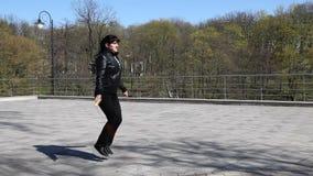 Corda de salto bonita nova da mulher em um parque da cidade filme