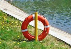 Corda de salvamento alaranjada perto da água O ` s da corda de salvamento no gancho fotografia de stock royalty free