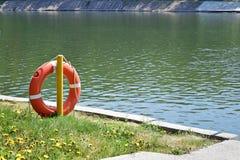 Corda de salvamento alaranjada perto da água O ` s da corda de salvamento no gancho Fotos de Stock Royalty Free
