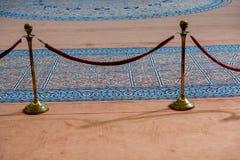 Corda de veludo e suporte do metal perto do tapete azul fotografia de stock