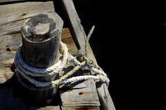 Corda del marinaio e nodo su un pilastro di legno alla spiaggia - backgound nero per scrivere fotografia stock