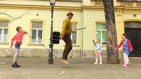 Corda dell'uomo anziano che salta con tre ragazze stock footage