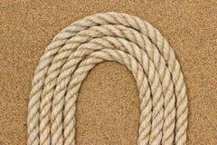 Corda della iuta sulla sabbia di mare Fondo fotografie stock libere da diritti