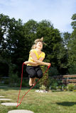 Corda di salto atletica della donna nel giardino Fotografia Stock