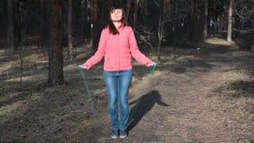 Corda di salto della donna di forma fisica La femmina sta pareggiando alla luce del giorno soleggiato negli alberi fondo, ragazza archivi video