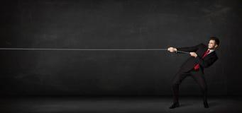 Corda di trazione dell'uomo d'affari su fondo grigio Fotografia Stock Libera da Diritti