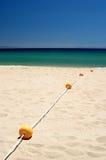 A corda do marcador amarelo buoys a condução na água desobstruída na praia arenosa ensolarada, branca em Spain. foto de stock royalty free