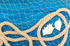 Corda e shell marinhos da rede em discos azuis Imagens de Stock Royalty Free