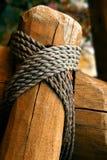 Corda legata intorno ad un palo di legno della rete fissa; DOF poco profondo Fotografie Stock