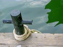 Corda nera di attracco del metallo con la corda bianca sul pilastro di legno trovato su un'isola immagini stock libere da diritti