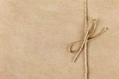 Corda o cordicella legata in un arco sulla carta kraft Fotografie Stock