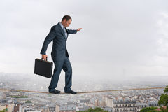 Corda per funamboli di camminata dell'uomo d'affari sopra la città Immagine Stock