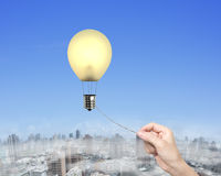 A corda puxando da mão da mulher conectou o balão de ar quente da ampola Fotografia de Stock