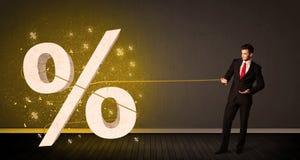 Corda puxando de homem de negócio com sinal procent grande do símbolo Fotografia de Stock Royalty Free