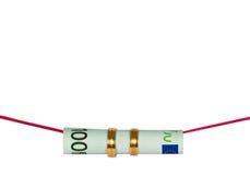 Corda rossa con 100euro e gli anelli di cerimonia nuziale Immagine Stock