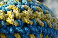 Cordage. Plaited ropes of blue and yellow color Royalty Free Stock Images