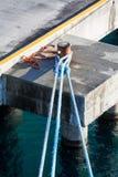 Cordas azuis gigantes amarradas a Rusty Bollard Fotos de Stock Royalty Free