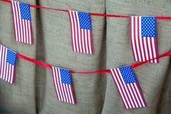 Cordas com as bandeiras americanas no fundo da lona Imagem de Stock Royalty Free