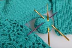 Cordas da linha para fazer malha a cor esmeralda e os ganchos para fazer malha Mentira em um produto feito malha pronto Fotos de Stock