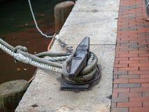 Cordas de um barco amarrado a um engate do grampo na área concreta do porto imagem de stock