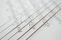 Cordas do instrumento do músico sob notas imagens de stock royalty free