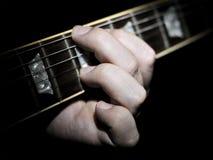 Cordas do manejo do jogador de guitarra em Fretboard Foto de Stock Royalty Free