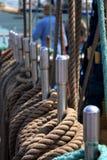 Cordas do marrom do navio nos trilhos com um homem no fundo fotografia de stock