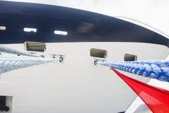 Cordas e bandeira vermelha no navio de cruzeiros azul e branco Imagens de Stock