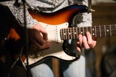 Cordas masculinas da guitarra da terra arrendada da mão na fase fotos de stock