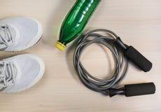 Corde à sauter avec les chaussures de sport et la bouteille de l'eau Photos libres de droits