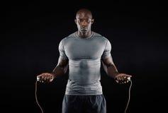 Corde à sauter d'homme masculin dans l'obscurité photographie stock