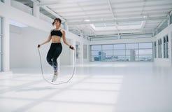 Corde à sauter de femme dans le studio de forme physique images libres de droits