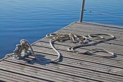 Corde attachée sur un bitt sur le dock en bois photo libre de droits
