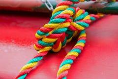 Corde colorée attachée dans un noeud sur une péniche rouge Photos stock